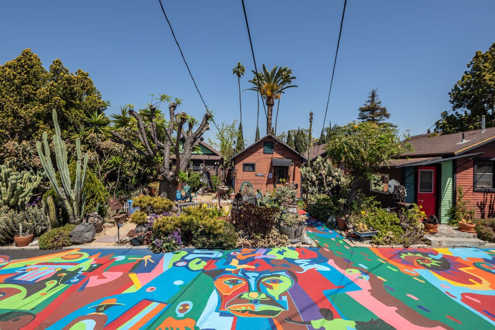 A brightly colored sidewalk in front of a few small houses, surrounded by lush vegetation