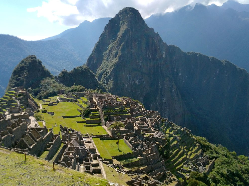 A panoramic view of Machu Picchu from above, with green slopes and angular mountain ridge in distance and the ruins of settlements along a sloping green mountainside; devoid of tourists