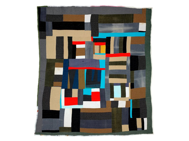 A quilt made of interlocking rectangles of dark green, gray, tan, with bright spots of light cyan, red and a tiny bit of yellow at the center