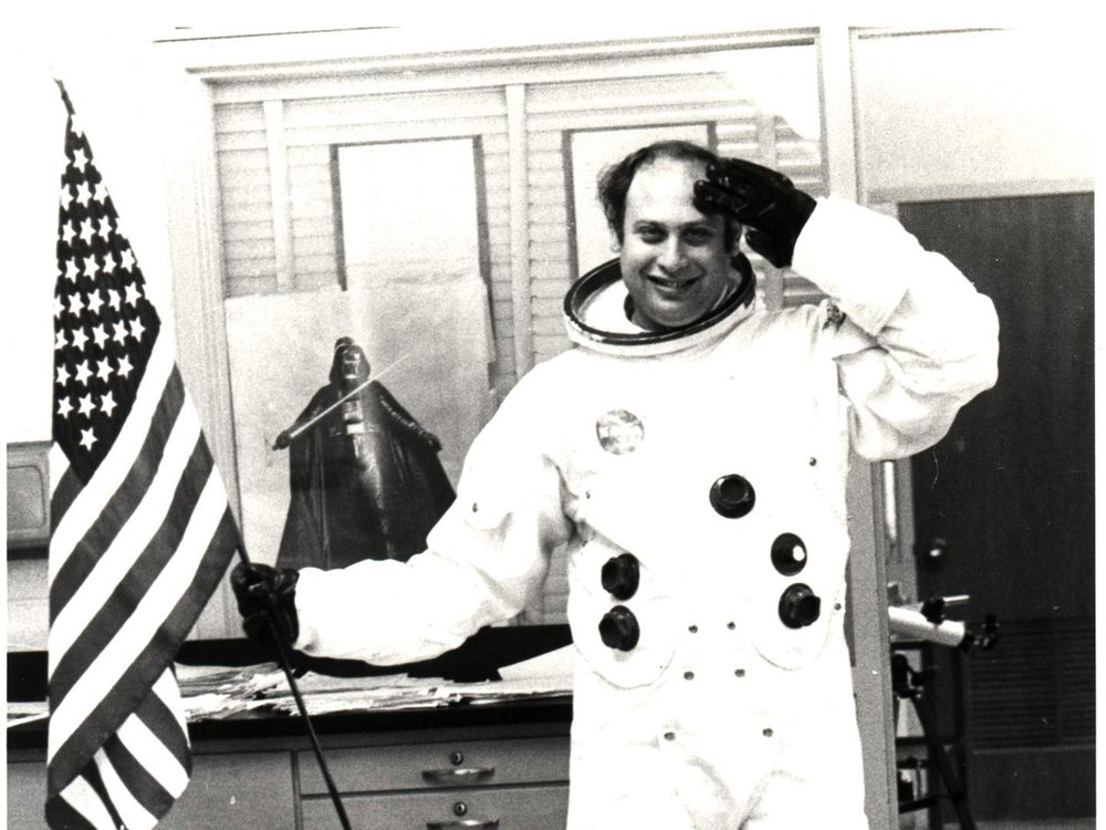 Informal classroom portrait of teacher Herbert Stephen Desind (1945-1992), wearing a reproduction Apollo-era spacesuit, holding an American flag; circa 1980s.  Desind was a space flight aficionado, and his collection of photographs of aircraft and spacecraft was donated to the National Air and Space Museum in 1997. This image is part of the Herbert Stephen Desind Collection.