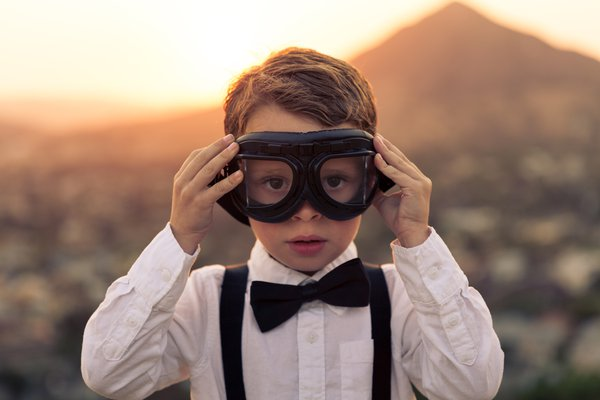 Boy with Flight Goggles on Mountain at Sunset overlooking city with Mountains in the background thumbnail