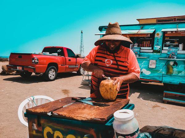 Smiling man preparing a coconut drink  thumbnail