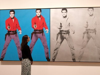 A gallery assistant poses with Andy Warhol's Elvis 1 and 2 1963-4 during a press preview for Tate Modern's retrospective on March 10, 2020.
