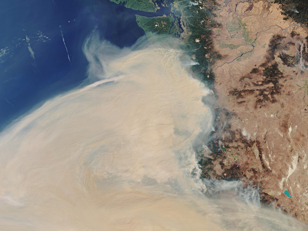 A satellite image shows wildfire smoke over the west coast of the United States