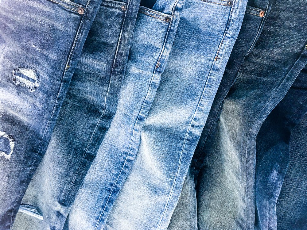 An assortment of different blue jeans laid on top of one another, including dark wash, light wash, and some with rips