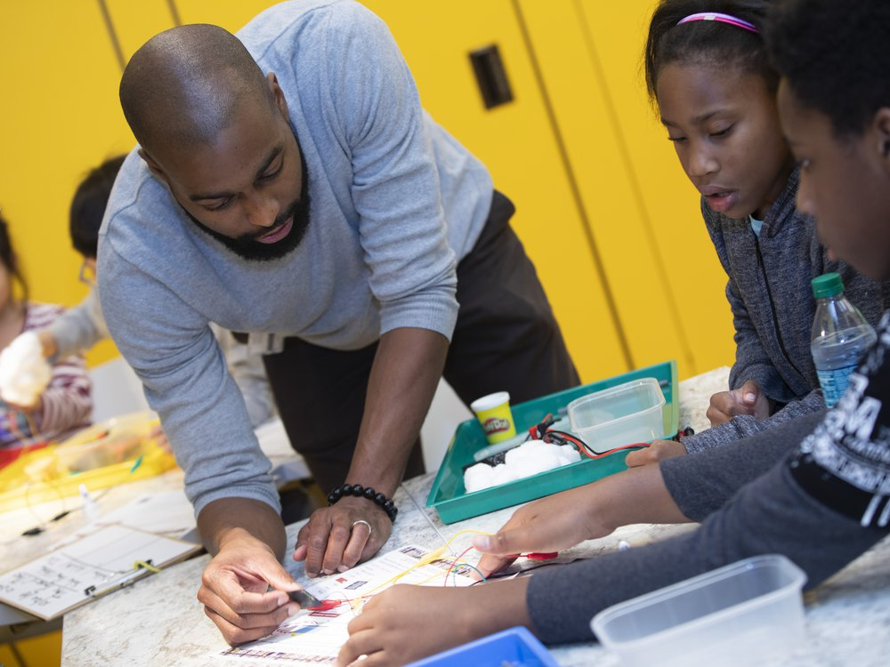 Museum educator Christopher Williams engages with student visitors during a Community Day in 2018. (Leah Jones, National Museum of African American History and Culture)