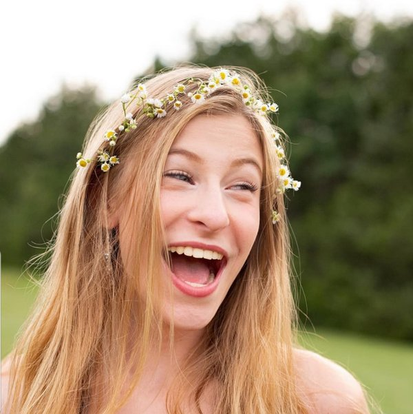 Girl laughing wearing a clover flower crown in her hair thumbnail