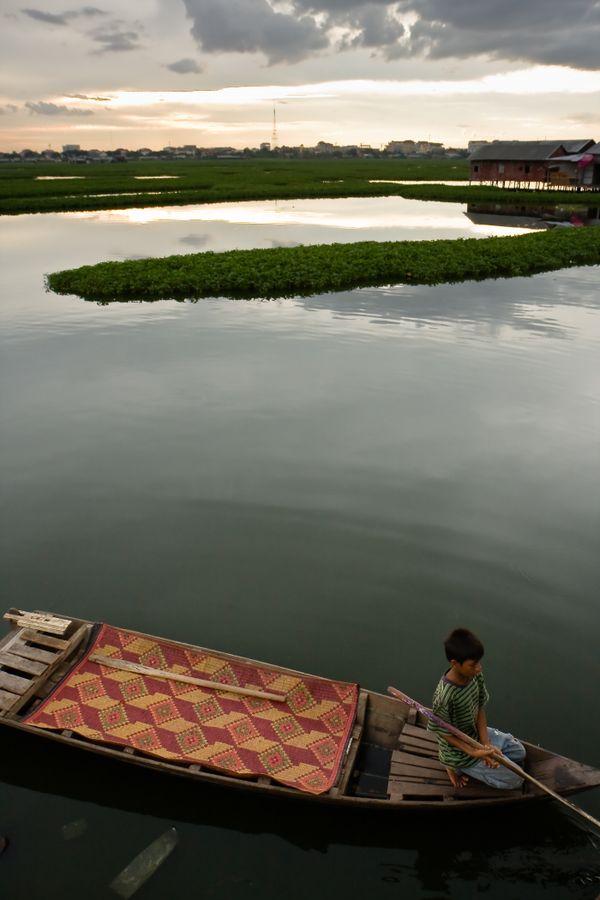 Boy touting dollar boat rides near poverty stricken stilt houses on Boeng Kak lake in Phnom Penh, Cambodia. thumbnail