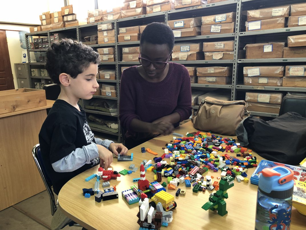 A young boy and an adult woman at a wooden table playing with multi-colored Legos.