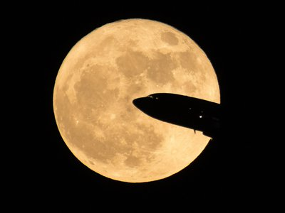 An aircraft takes off from Ronald Reagan National Airport, passing in front of the Moon as it rises above Washington D.C.