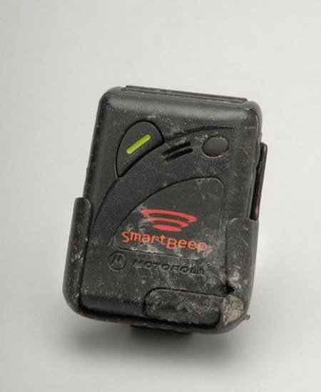 An old rectangular black beeper that shows signs of damage and dirt