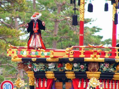 A marionette performs atop a Matsuri float