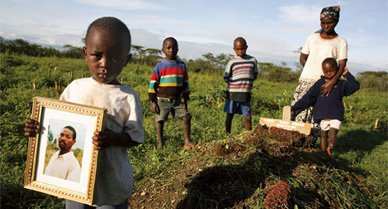 Jokim Githuka, 3, displays a portrait of his dead father, Robert Njoya, in a Kenyan maize field. Other sons stand by his grave with Njoya's widow, Serah. The trial of his undisputed killer, Thomas Cholmondely, has electrified this former British colony.