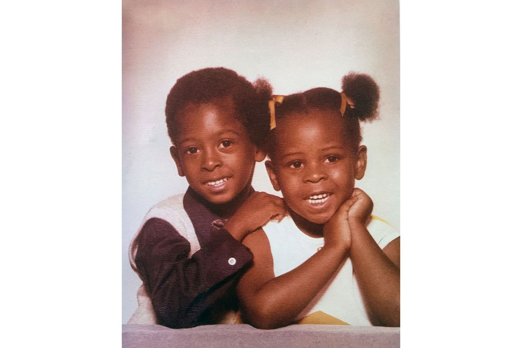 Old studio portrait of young brother and sister, dressed up and smiling.