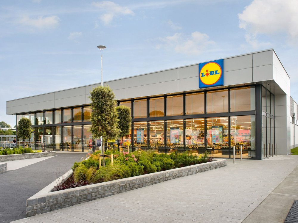 An image of a brightly lit new Lidl store; a large square building with the store's logo, a blue square with a yellow circle and blue and red block text that reads LIDL; surrounded by pavement and a parking lot