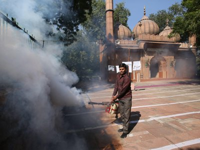 An Indian Municipal Corporation sanitation worker fumigates as part of a drive to curb breeding sites for mosquitoes causing a dengue outbreak in New Delhi in October 2015.
