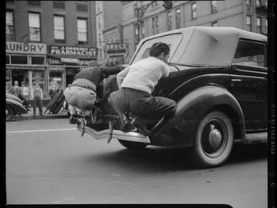 Men riding on the back of a car, 1940.