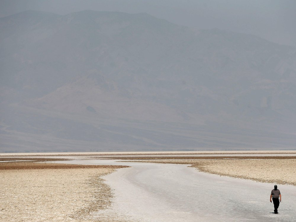 A large expanse of flat, sandy ground, with the faint outline of a hill rising in the distance; one lone traveler is walking in the lower righthand corner of the frame, looking very small compared to the landscape
