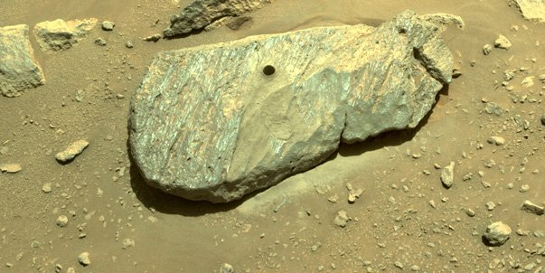 An image of a boulder with a hole drilled into it. The photo was taken by the Mars rover on Planet Mars and shows where the rover obtained its first rock sample from.
