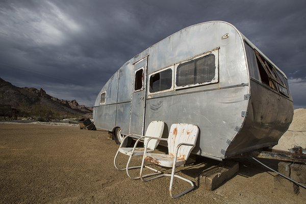 The road not traveled - an old camper and chairs out in the desert. thumbnail