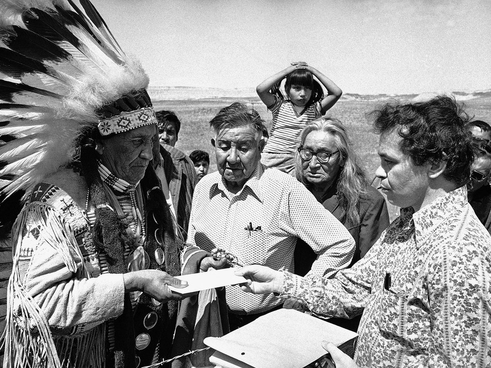 Hank Adams carries a letter from the White House to Chief Frank Fools Crow (Oglala Lakota) during the siege of Wounded Knee. Pine Ridge Reservation, South Dakota, 1973. (Hank Adams Collection)