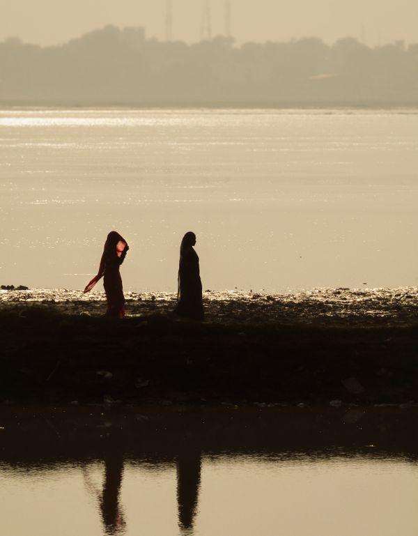 Two women walking on the path near Ganga river thumbnail