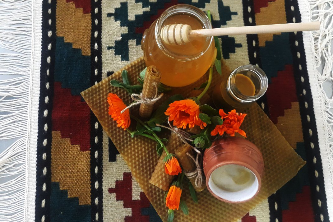 Atop a geometric patterned blanket is carefully arranged a spread of beeswax, honey in jars, honey cream in a terracotta pot, and orange flowers.
