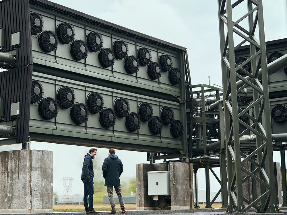 Two men stand in front of tall wall of fans at the Orca carbon capture facility in Iceland