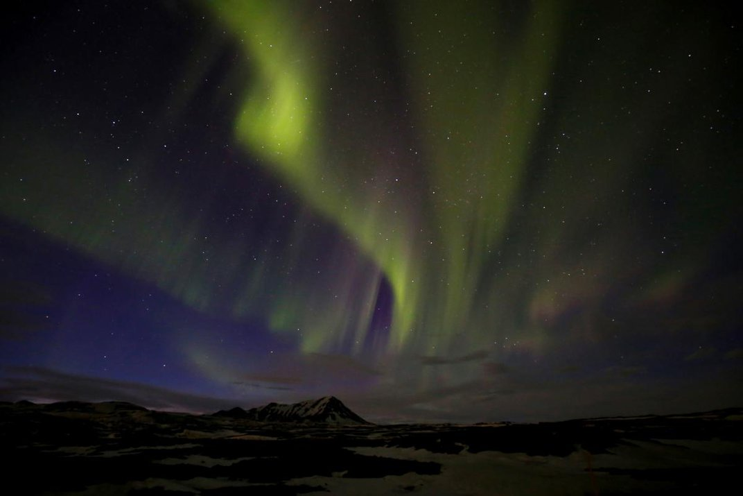 A photograph of the northern lights over a mountain in the distance.