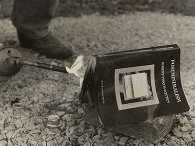 Lorna Truck and Tim Benson. Photograph documenting burning of Robert Pincus-Witten's book Postminimalism (1977) at the request of artist Buster Cleveland as part of the 1979 Des Moines Festival of the Avant-Garde, circa 1979.
