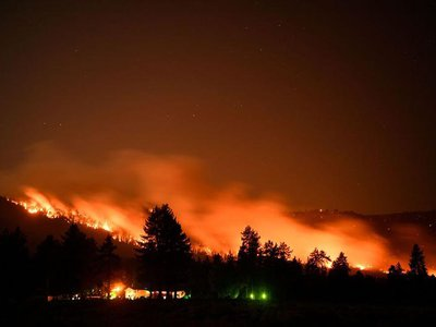 In this long exposure picture, trees burn on a hillside behind Honey Lake campground during the Dixie Fire on August 18, 2021 in Milford, California. The wildfire in Northern California continues to grow, burning over 626,000 acres according to CalFire.