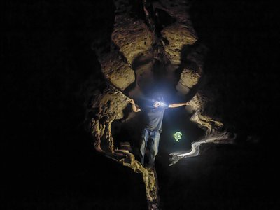 Dr. Maxime Aubert, archeologist and geochemist, uses his headlamp to examine the cave art at Leang Lompoa in Maros, Indonesia.