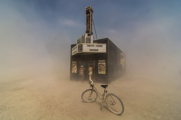 "Dust swirls around citizens of Black Rock City as they peek into the ""Black Rock Bijou Theatre"", an art installation at the 2013 Burning Man festival. thumbnail"