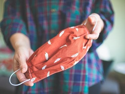 A person holds a sewn handmade fabric mask.