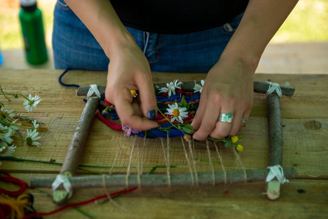 A person weaves on a handmade loom made from sticks tied together with twine.