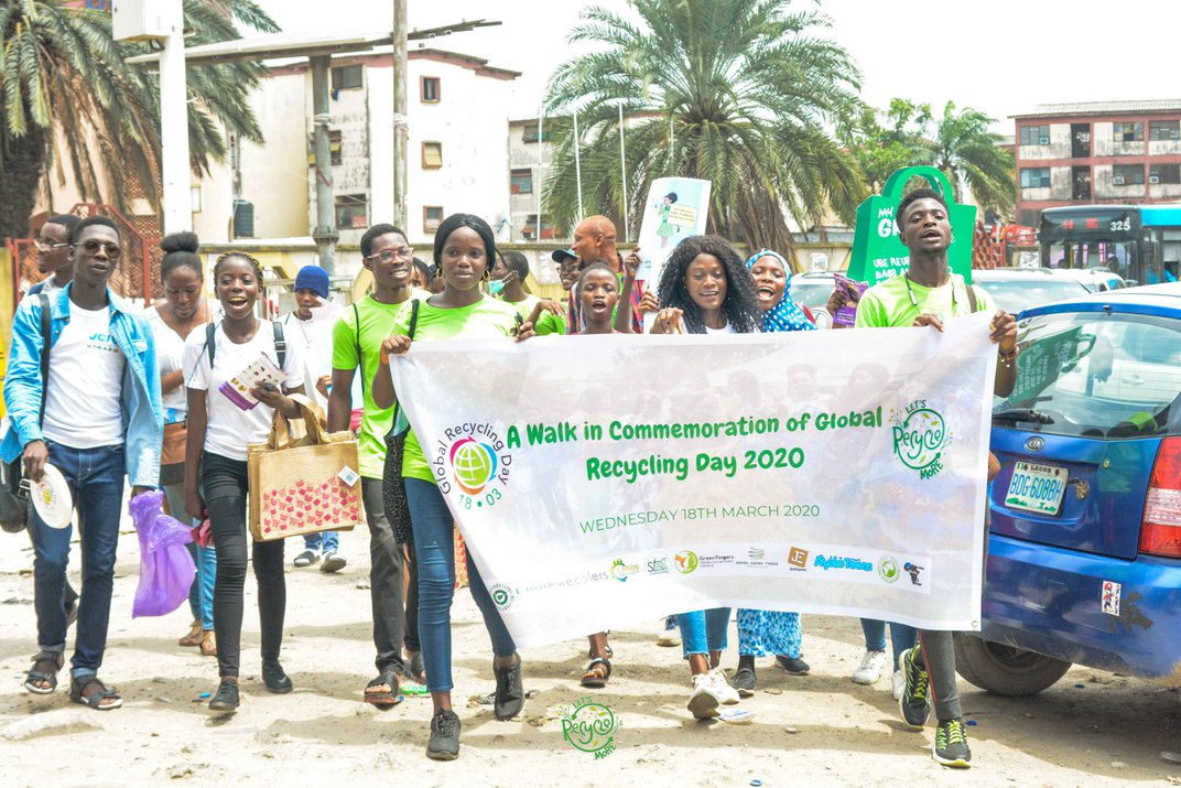 students walk together holding a banner for World Recycling Day