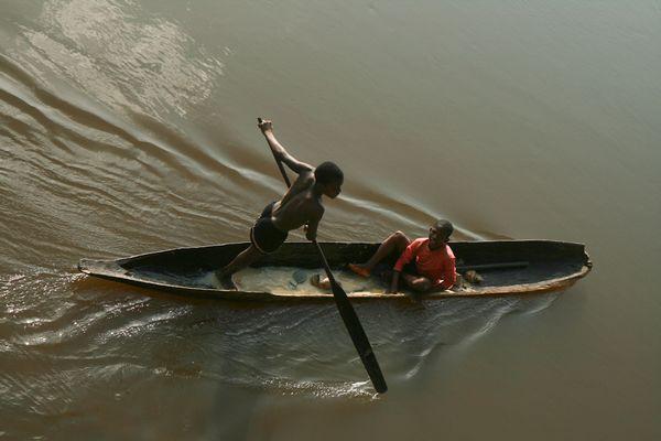 Paddling dugout canoe on Sangha River. thumbnail