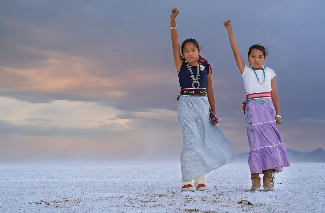 Two children stand, each with one arm raised.
