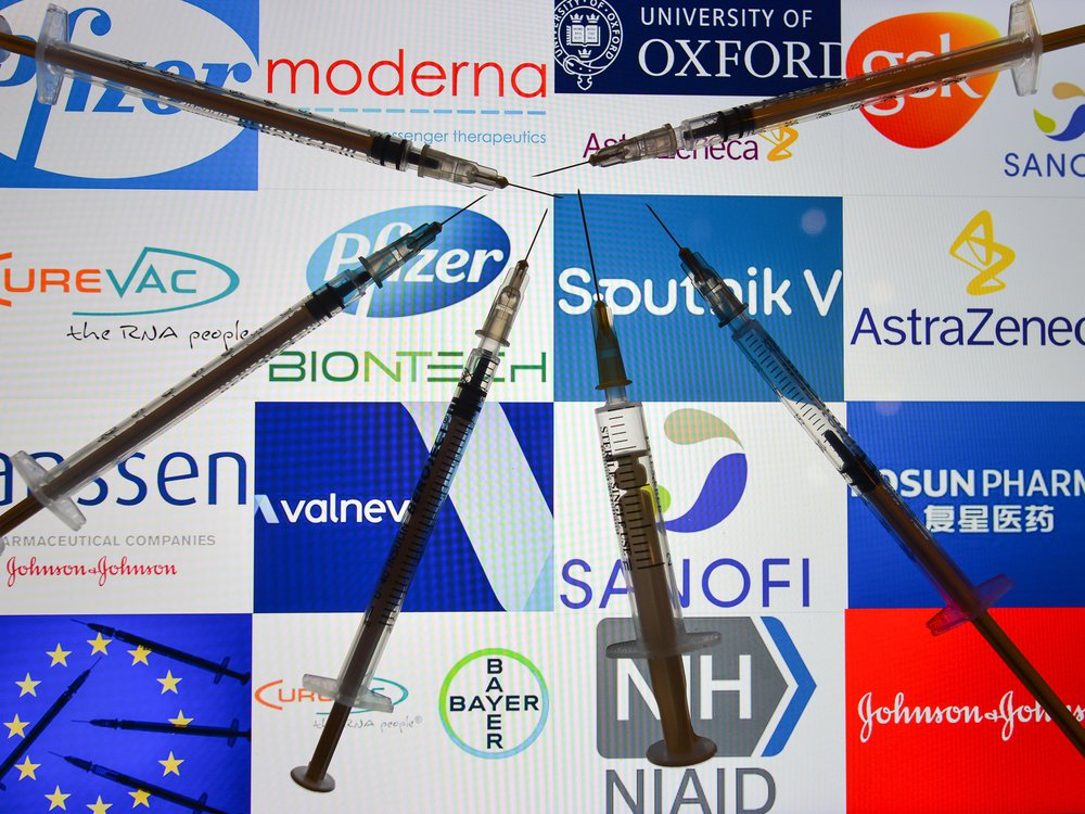 An illustrative image of medical syringes in front of the logos of various companies working on the Covid-19 vaccine, displayed on a screen.