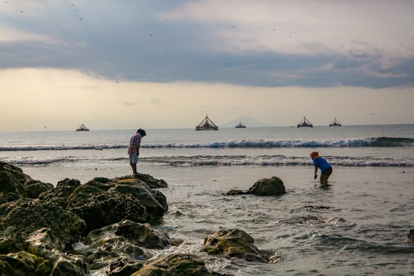 Two women looking for sea resources before sunset at Tanjung Lesung beach, Indonesia. thumbnail