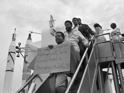 Reverend Ralph Abernathy, flanked by associates, stand on steps of a mockup of the lunar module displaying a protest sign while demonstrating at the Apollo 11 launch.