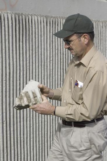 Man in baseball cap holding a baseball glove-sized chunk of concrete