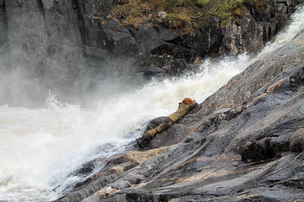 A girl takes pictures of a waterfall thumbnail