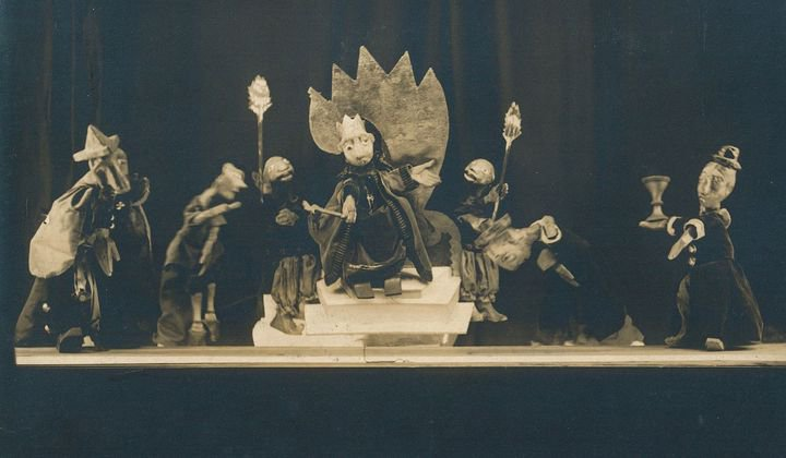 Several puppets on a stage, with a king on a throne in the center. Black-and-white photo.