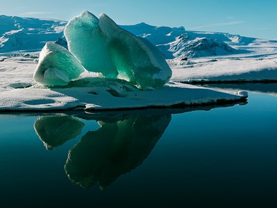 Lake Jökulsárlón shimmers with the reflection of a magnificent iceberg. This lake, located at the edge of Vatnajökull, Iceland's largest ice cap, formed slowly when part of the glacier began to recede in the 1920s. The glacier continues to calve (split), releasing more icebergs into the expanding lake.