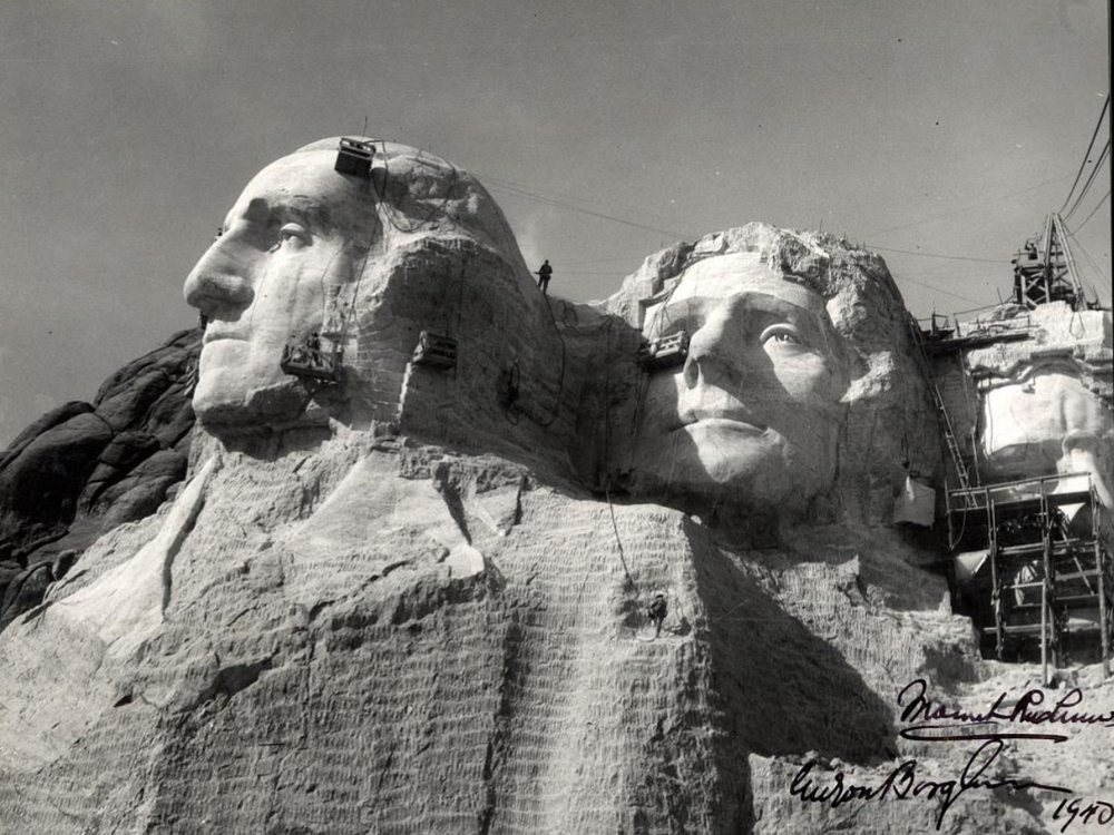 A close up view of workers carving the heads of George Washington and Thomas Jefferson on Mount Rushmore