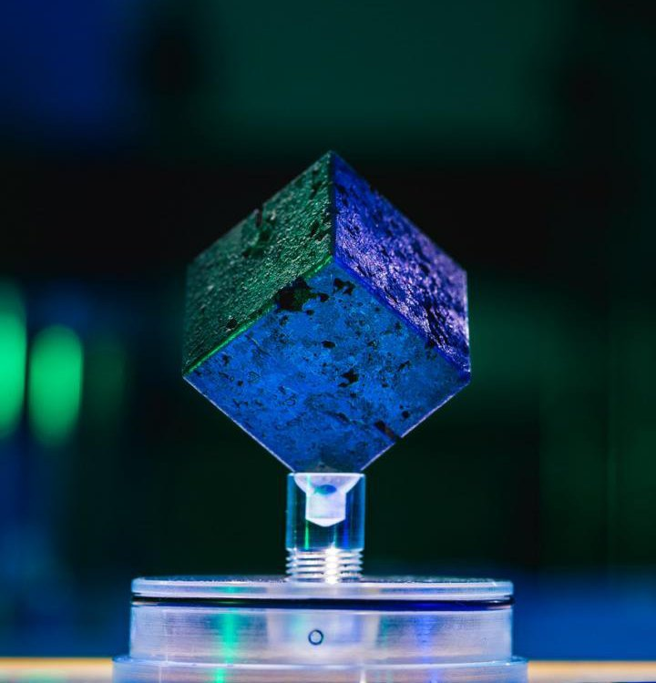 A blue and green image of a small metal cube resting on a display, with colored lights in the background