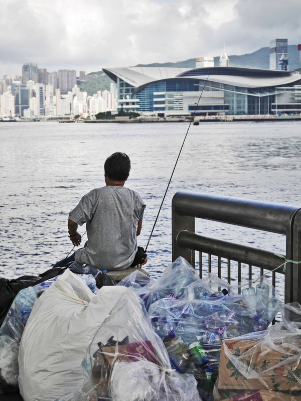 A man tries to fish along the harbor in Hong Kong amidst trash with the HK Convention & Exhibition Center in the background. thumbnail