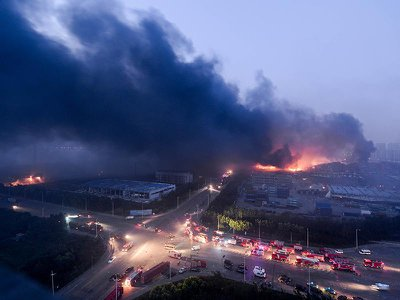 Dense smoke rises as fire engines arrive at the blast site after the deadly explosions in Binhai New Area in Tianjin, China.