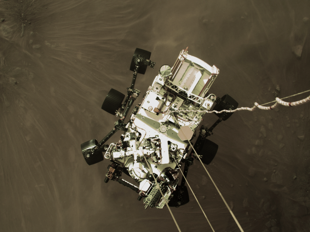 A photo taken during Perseverance's landing shows it dangling from cords above the surface of Mars
